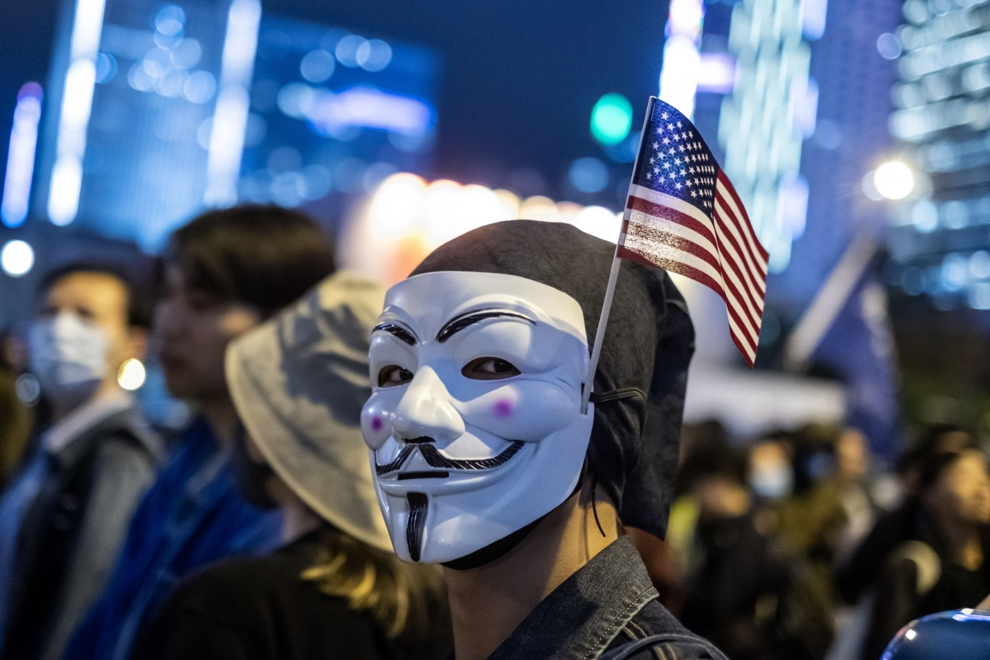 """A demonstrator wears an anonymous mask, also known as a Guy Fawkes mask, and an American flag during the """"Thanksgiving Day Assembly for Hong Kong Human Rights and Democracy Act"""" at Edinburgh Place in the Central district of Hong Kong, China, on Thursday, Nov. 28, 2019. (Justin Chin/Bloomberg)"""