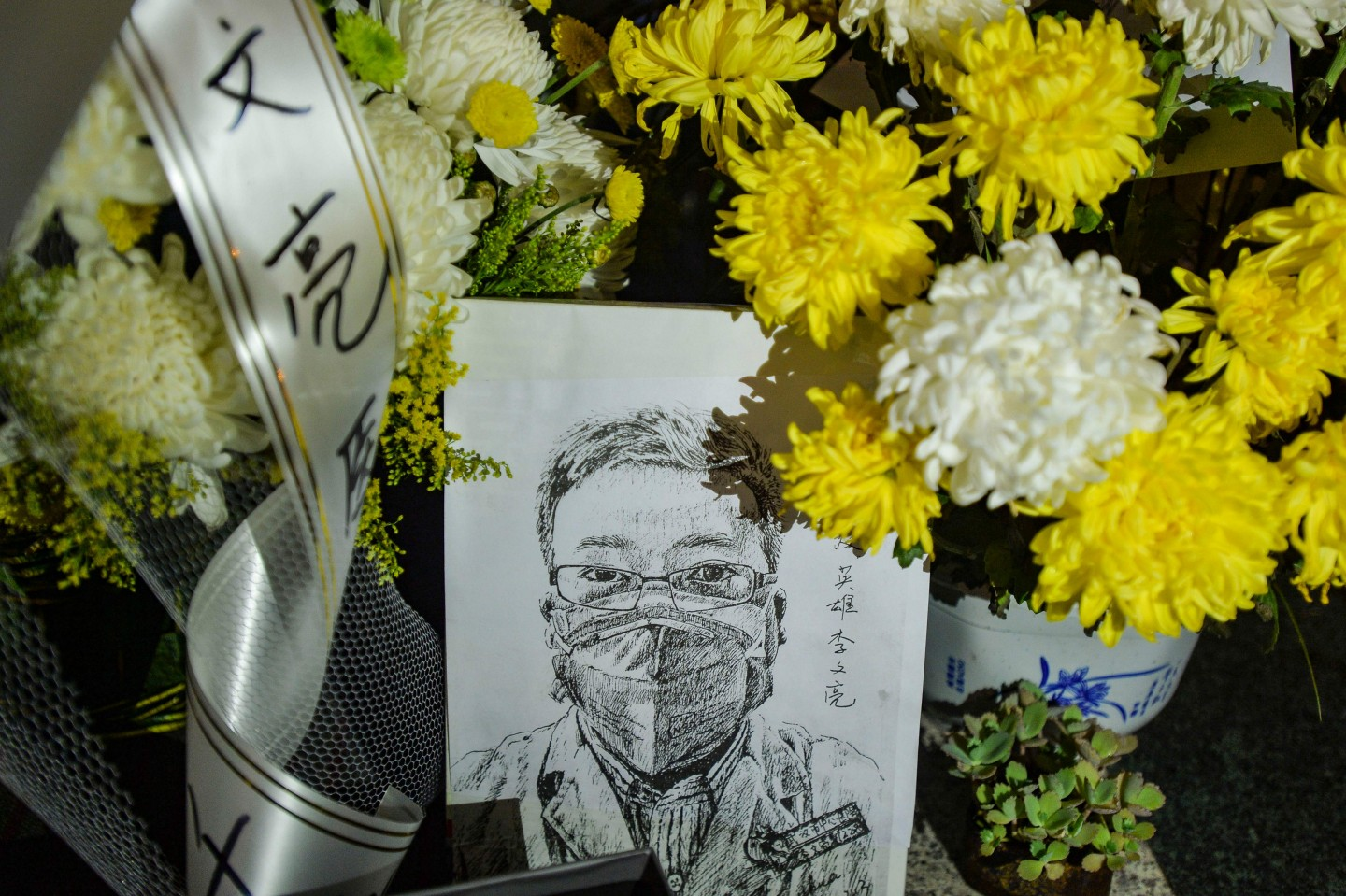 This photo taken on 7 February 2020 shows a photo of the late ophthalmologist Li Wenliang with flower bouquets at the Houhu Branch of Wuhan Central Hospital. (STR/AFP)