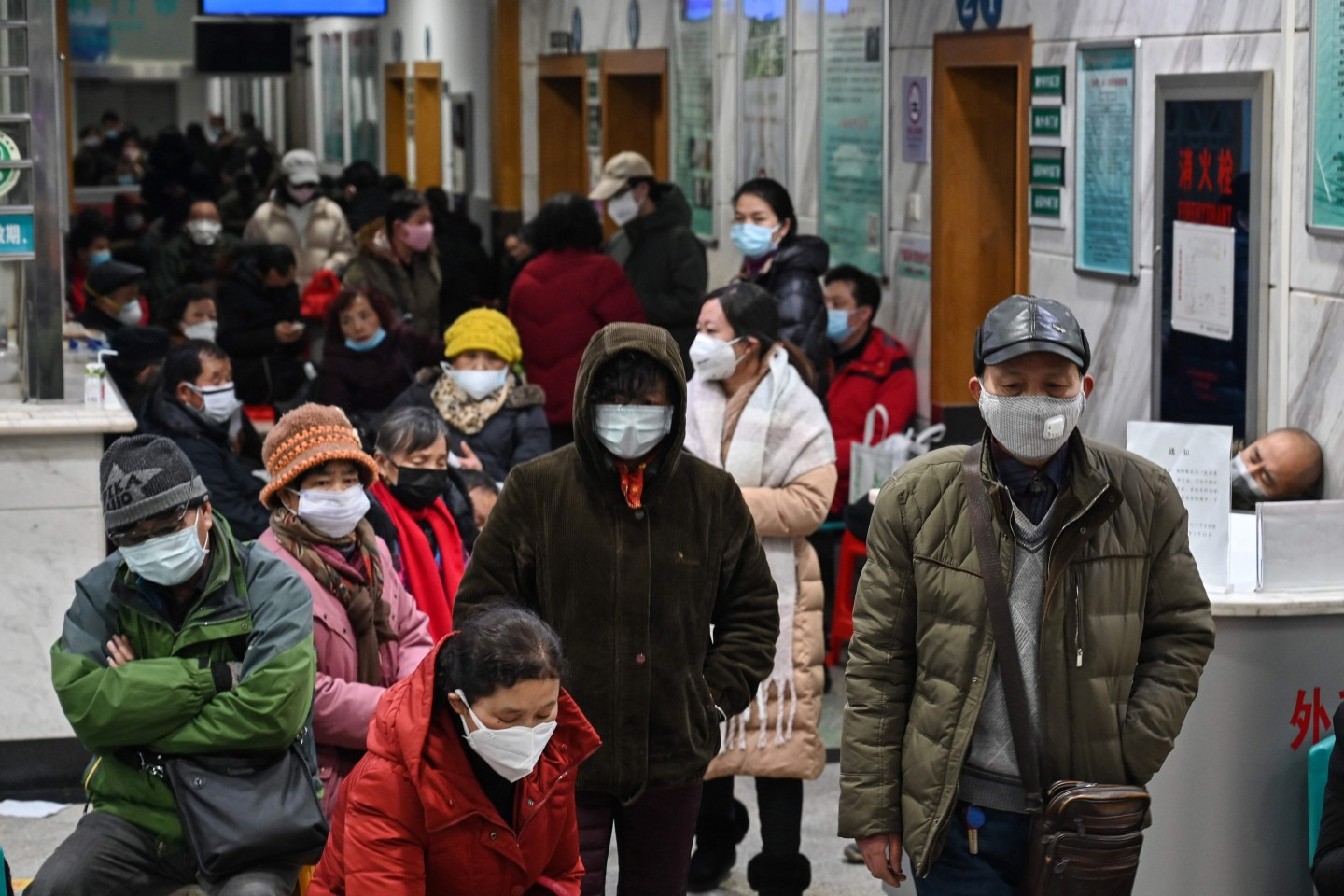 People wearing face masks to help stop the spread of a deadly virus which began in the city, wait for medical attention at Wuhan Red Cross Hospital in Wuhan on 25 January 2020. (Hector Retamal/AFP)