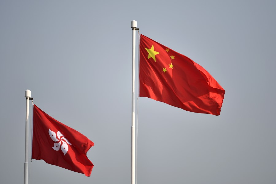 The Chinese national flag (right) flies alongside the Hong Kong flag. (Anthony Wallace/AFP)