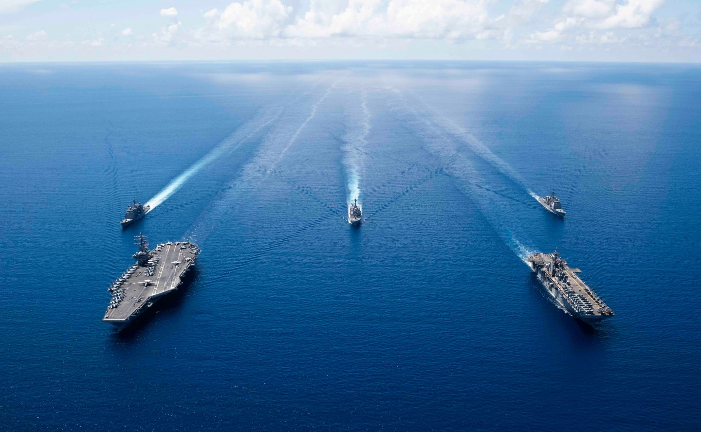 This US Navy photo obtained October 7, 2019 shows the aircraft carrier USS Ronald Reagan (CVN 76)(L), and the amphibious assault ship USS Boxer (LHD 6) and ships from the Ronald Reagan Carrier Strike Group and the Boxer Amphibious Ready Group underway in formation while conducting security and stability operations in the US 7th Fleet area of operations on October 6, 2019 in the South China Sea. (AFP/US Navy/Erwin Jacob V. Miciano/Handout)