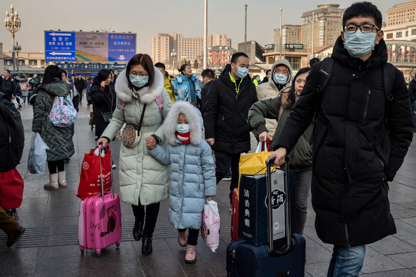 The outbreak of the Wuhan coronavirus is rapidly escalating. In this photo taken on 21 January 2020, people wearing protective masks are seen arriving at Beijing railway station to head home for the Lunar New Year. (Nicolas Asfouri/AFP)