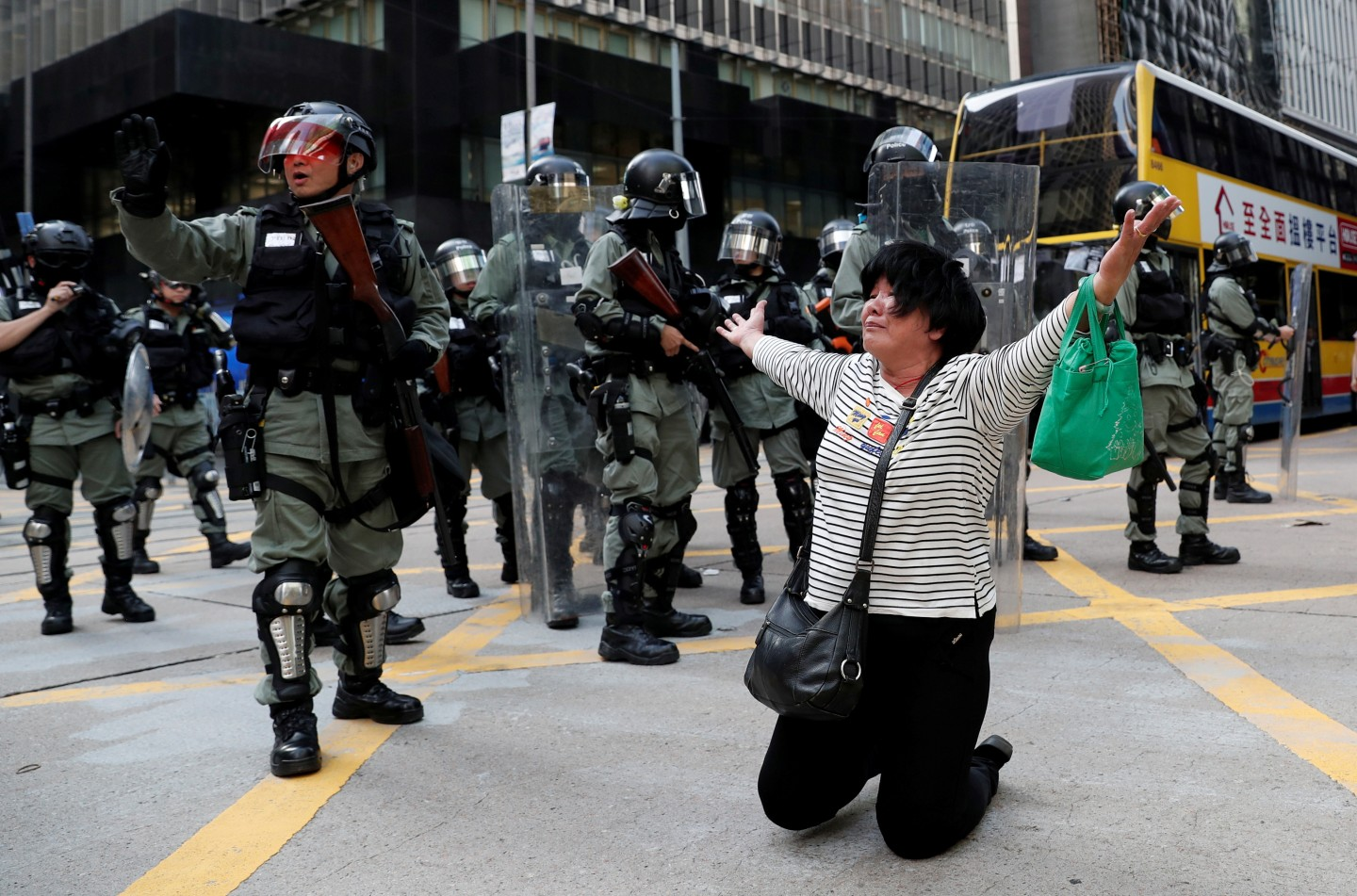 A woman cries and prays in front of riot police during an anti-government protest in Central on November 12, 2019. (REUTERS/Shannon Stapleton)