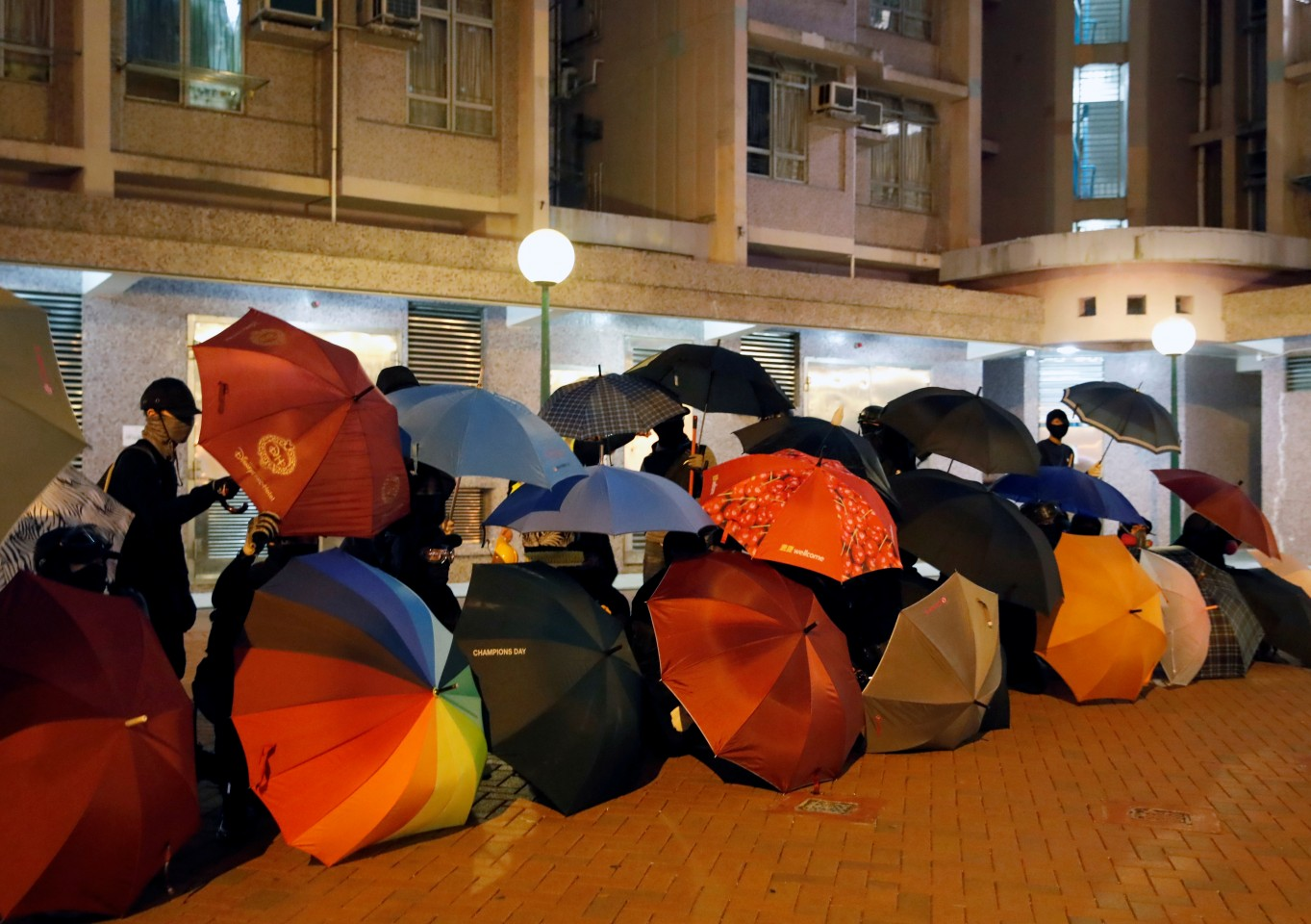 Anti-government protesters shield themselves with umbrellas during a protest in Hong Kong on 8 January 2020. (Navesh Chitrakar/Reuters)