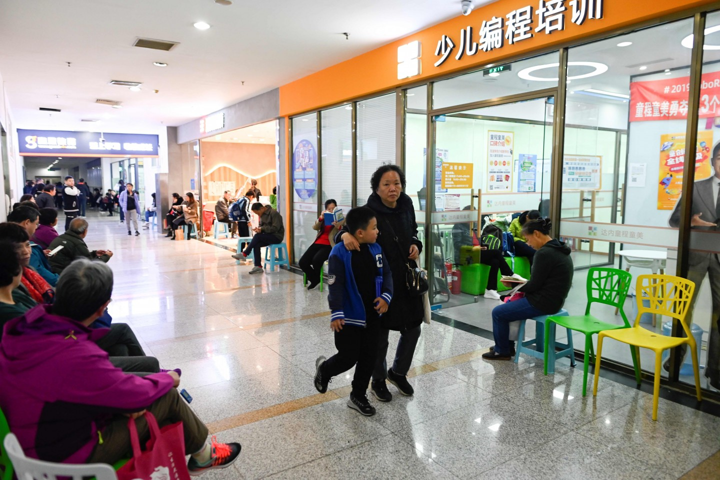 China has been making huge investments in robotics and AI, with the government issuing in 2017 an AI development plan which suggested programming courses be taught in both primary and secondary schools. This picture taken on November 8, 2019 shows parents and guardians waiting outside a children's computer coding training centre in Beijing.  (Wang Zhao/AFP)