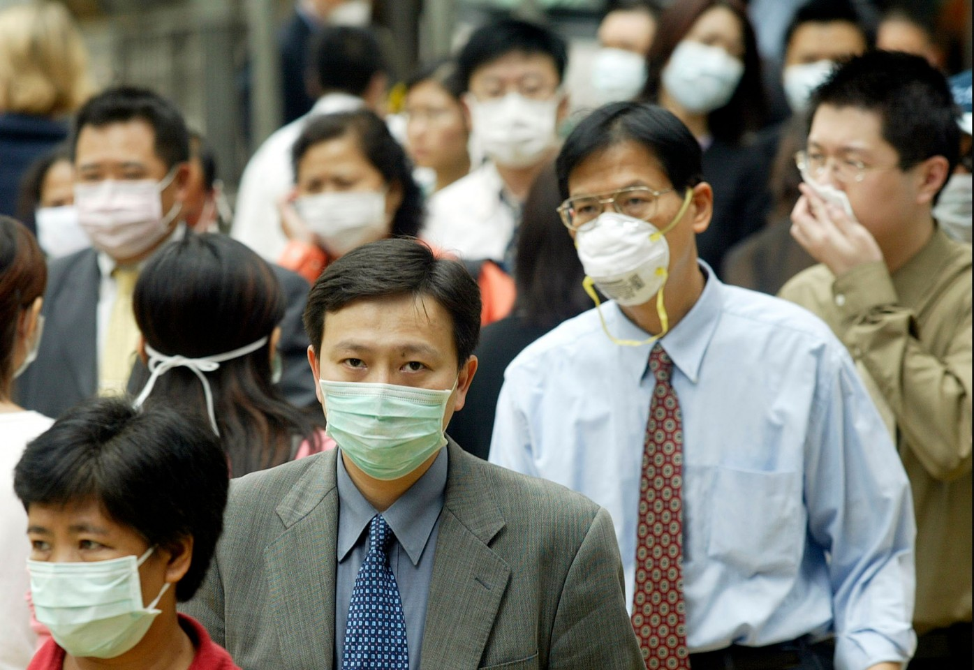 This file photo taken on 31 March 2003 shows pedestrians wearing masks on the street to protect against the SARS virus in Hong Kong. (Peter Parks/AFP)
