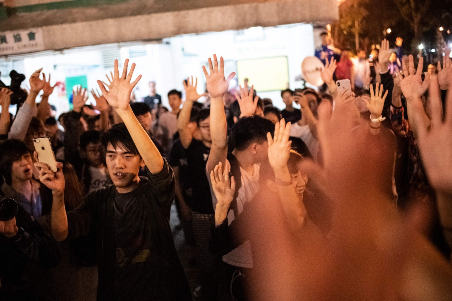 Pro-democracy supporters celebrate after pro-Beijing candidate Junius Ho lost a seat in the district council elections in Tuen Mun district of Hong Kong, early on November 25, 2019. - Hong Kong's voters turned out in record numbers for local council elections that the city's pro-democracy movement hopes will add pressure on the Beijing-backed government to heed their demands after months of violent protest. Lengthy queues snaked out of polling stations across the territory in the election for 18 district councils, where high turnout is expected to benefit democratic forces. (Photo by Philip FONG / AFP)
