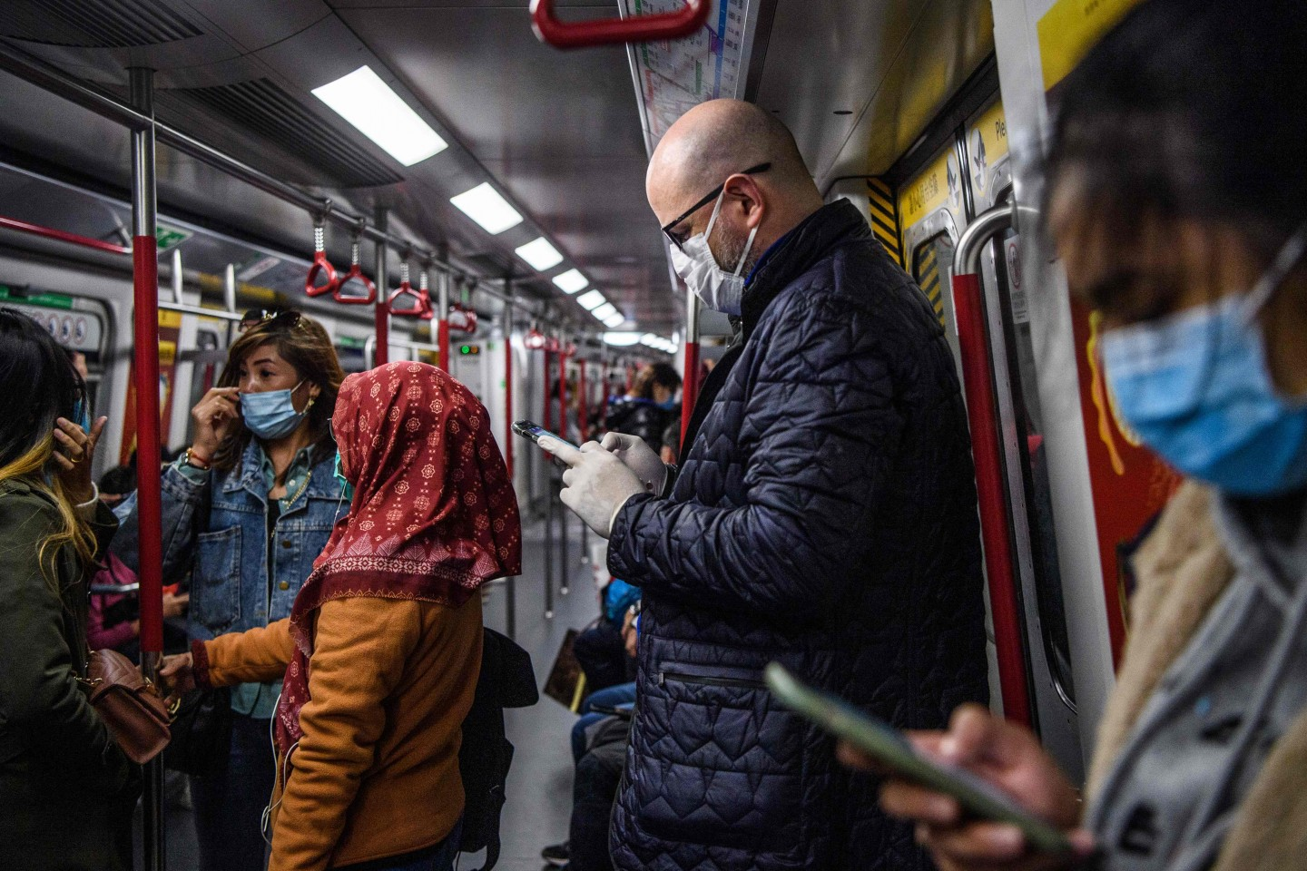 Hong Konger's awareness of virus outbreaks has greatly increased since the 2003 SARS epidemic. Pictured here are passengers wearing face masks while travelling on a MTR in Hong Kong on 27 January 2020 as a preventative measure following the coronavirus outbreak which began in the Chinese city of Wuhan. (Anthony Wallace/AFP)