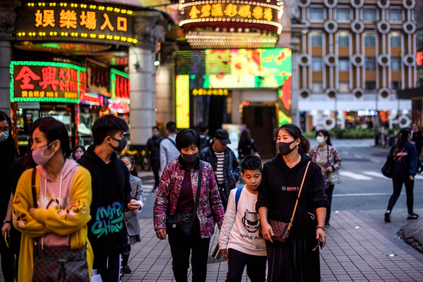 Pedestrians wear face masks as they walk along a pavement in Macao on 22 January 2020, after the former Portuguese colony reported its first case of the new SARS-like virus that originated from Wuhan in China. (Anthony Wallace/AFP)