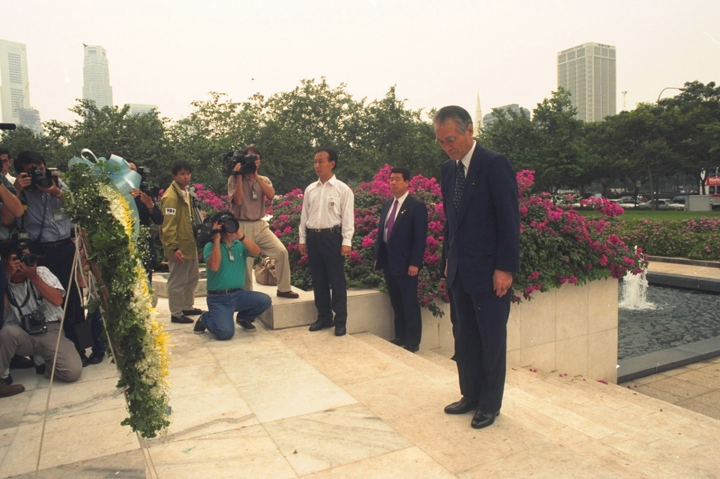 In 1994, Japanese Prime Minister Tomiichi Murayama visited the memorial for Singaporean civilians killed during the Japanese Occupation. After a moment's silence at the foot of the memorial, he bowed briefly before walking up the steps leading to the four columns of the memorial. He then placed a wreath at the base of the columns, bowed again, and remained in the silent, bowed position for about a minute. (SPH)