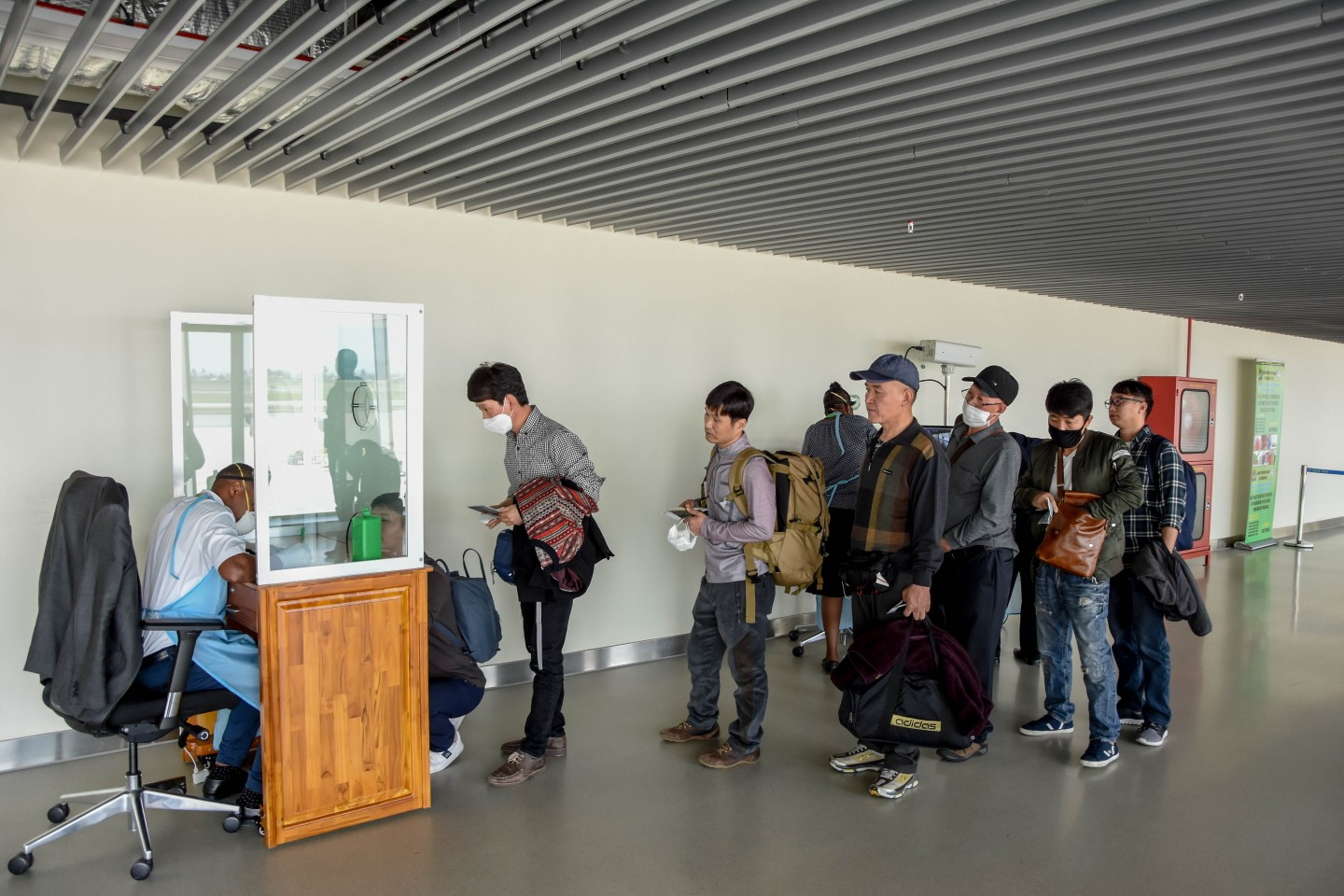 Passengers arriving from China wait in line to be checked by health officials at the Julius Nyerere International Airport in Dar Es Salaam on 29 January 2020. (Ericky Boniphace/AFP)