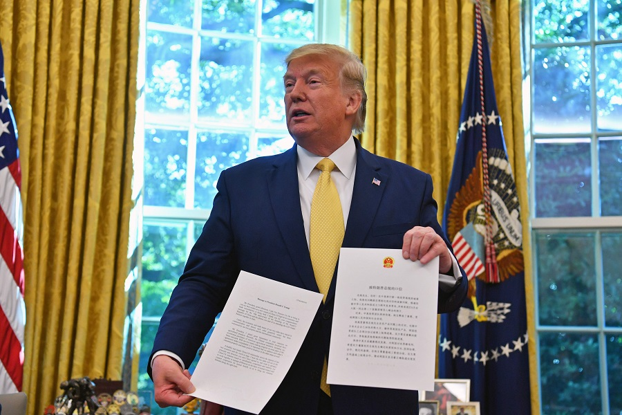 """US President DonaldTrumpshowing a letter from Chinese PresidentXiJinpingwhen he announced an""""initial deal"""" back in October 2019. (Nicholas Kamm/AFP)"""