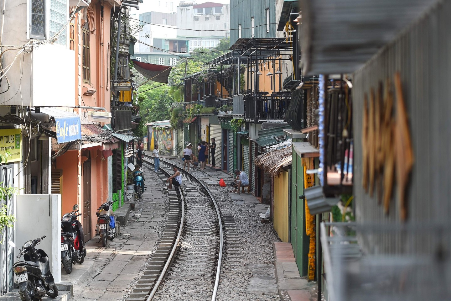 """Vietnam has a seemingly insatiable appetite for domestic infrastructure investment. A resident sits on Hanoi's popular train street on October 10, 2019 following a municipal authorities order to deal with cafes and """"ensure safety"""" on the railway track. (Photo by Nhac NGUYEN / AFP)"""