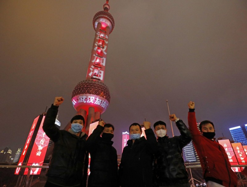 """Tourists pose with the Oriental Pearl TV Tower in the background on 8 Feb 2020. Slogans with the words """"武汉加油"""" (Wuhan, you can do it!) wrap the Shanghai landmark. (CNS)"""