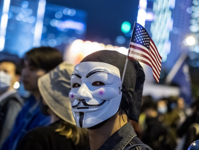 "A demonstrator wears an anonymous mask, also known as a Guy Fawkes mask, and an American flag during the ""Thanksgiving Day Assembly for Hong Kong Human Rights and Democracy Act"" at Edinburgh Place in the Central district of Hong Kong, China, on Thursday, Nov. 28, 2019. (Justin Chin/Bloomberg)"