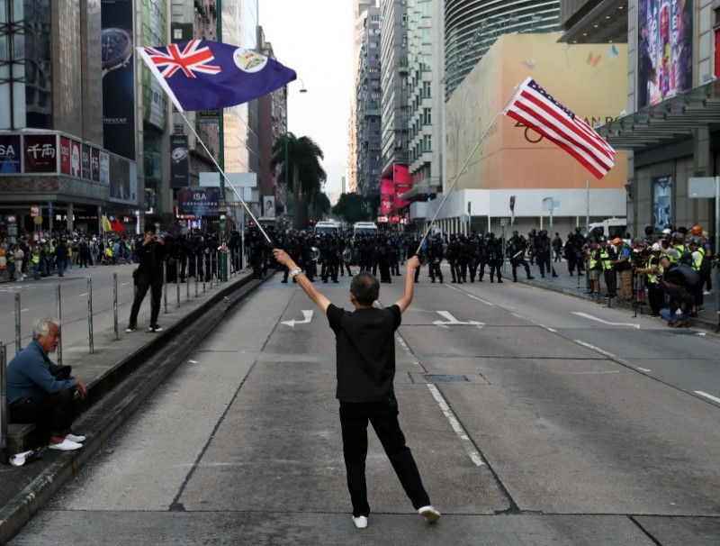 A protester waves a US and a colonial Hong Kong flag at a rally in Hong Kong. (Leah Millis/REUTERS)