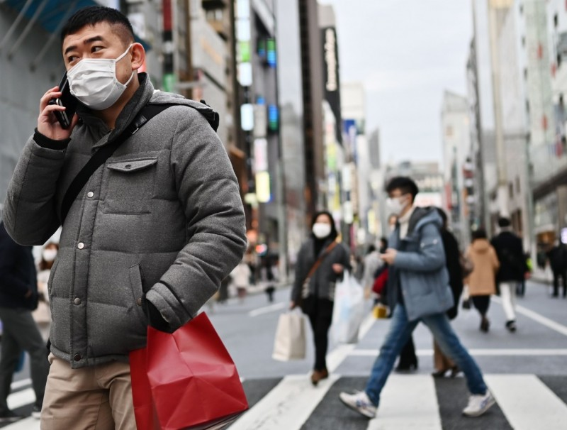 Pedestrians wearing protective masks to help stop the spread of Covid-19, walk on a street in Tokyo's Ginza area on 25 January 2020. (Charly Triballeau/AFP)
