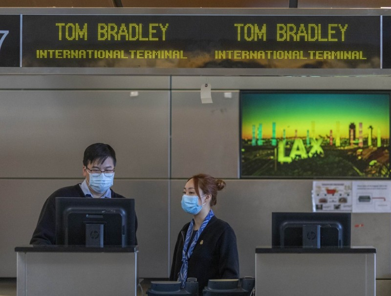 Air China employees wear medical masks for protection against the Covid-19 at LAX Tom Bradley International Terminal on 2 February 2020 in Los Angeles, California. The United States was first to announce a travel ban on travellers from China. (David McNew/Getty Images/AFP)