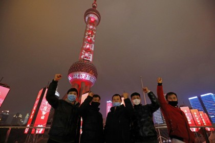 "Tourists pose with the Oriental Pearl TV Tower in the background on 8 Feb 2020. Slogans with the words ""武汉加油"" (Wuhan, you can do it!) wrap the Shanghai landmark. (CNS)"