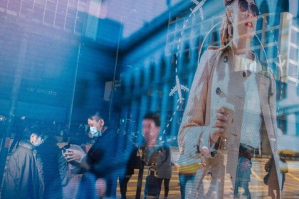 Pedestrians wearing protective masks are reflected in an advertisement in the Central district of Hong Kong, January 29, 2020. (Paul Yeung/Bloomberg)