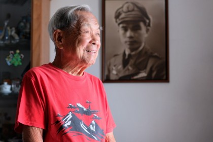 Centenarian Ho Weng Toh is not only a WWII veteran, SIA pioneer pilot, but also a published author of his autobiography. A picture of him taken in 1945, hangs on the wall. (Long Kwok Hong/SPH)