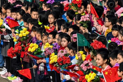 "The Chinese system has governance capacity to tackle the emerging ""troubled times"". This picture shows children waiting to bid farewell to China's President Xi Jinping and his wife Peng Liyuan at the international airport in Macau on 20 December, 2019.  (Photo by Eduardo Leal/AFP)"